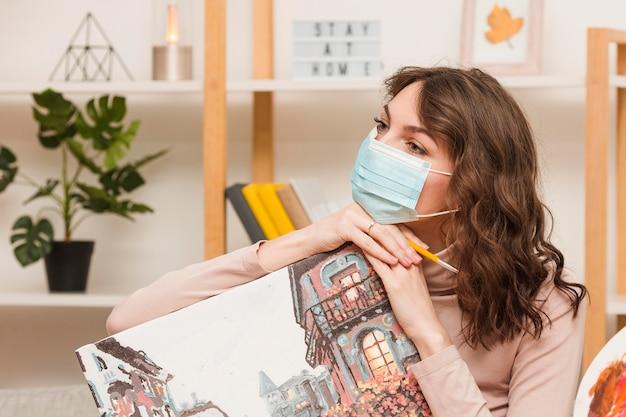 Młoda kobieta z maskowym mienie obrazkiem