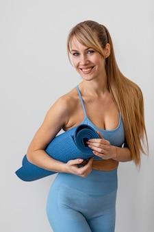 Młoda kobieta z matą do jogi
