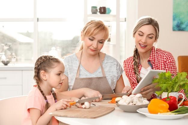 Młoda kobieta z matką i córką gotuje w kuchni