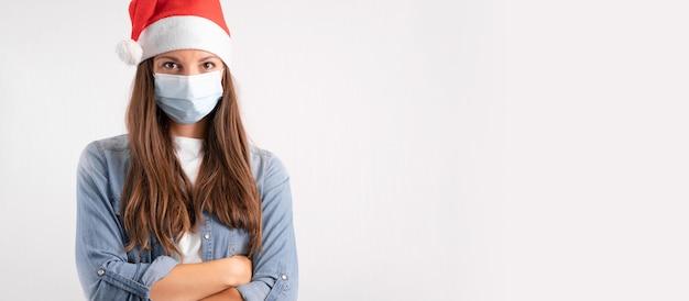 Młoda kobieta z medyczną maską i santa hat