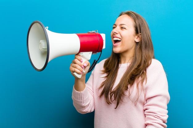 Młoda kobieta z megafonem przeciw błękitnemu tłu