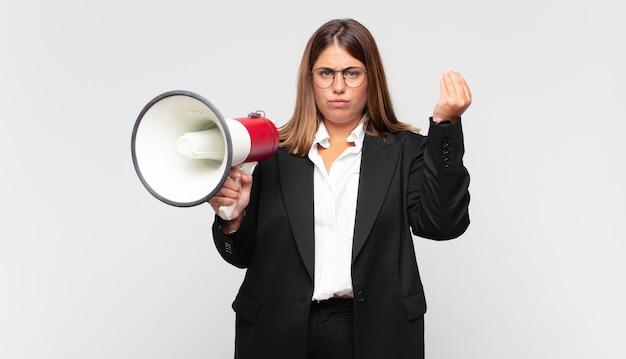 Młoda kobieta z megafonem robi gest kaprysu lub pieniędzy, każe ci spłacić swoje długi!