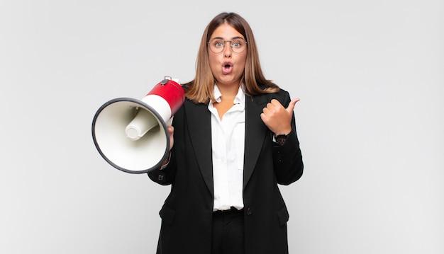 Młoda kobieta z megafonem wyglądająca na zdumioną z niedowierzaniem, wskazująca na obiekt z boku i mówiąca wow, niewiarygodne