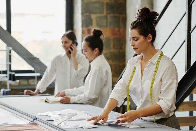 Młoda kobieta z miarką biorąc wzór papieru ze stołu, idąc do pracy nad elementem nowej kolekcji mody