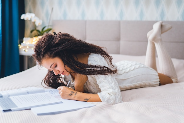 Młoda kobieta z mieszanymi włosami afro w domowych ubraniach leży na łóżku i ma lekcję online z tabletem. nauka na odległość lub koncepcja pracy,