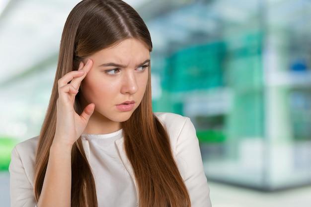 Młoda kobieta z migreny mienia głową