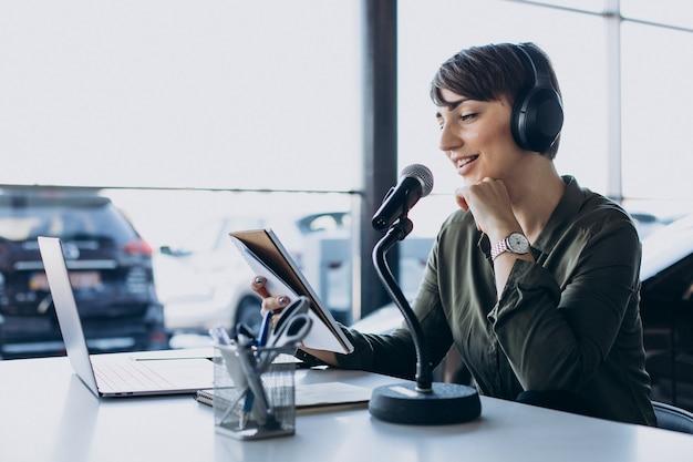 Młoda kobieta z mikrofonem nagrywa głos