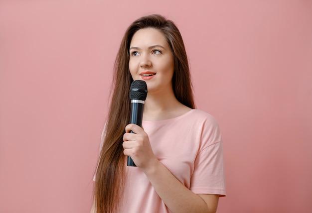 Młoda kobieta z mikrofonem w ręku na różowo