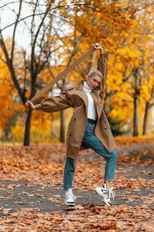 Młoda kobieta z modną fryzurą w eleganckim płaszczu pozuje na świeżym powietrzu w parku