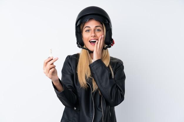 Młoda kobieta z motocykla hełmem nad odosobnioną biel ścianą