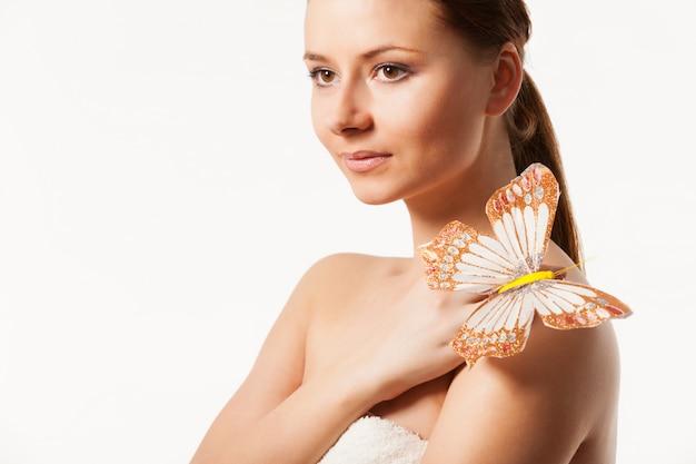 Młoda kobieta z motylem na ramieniu.