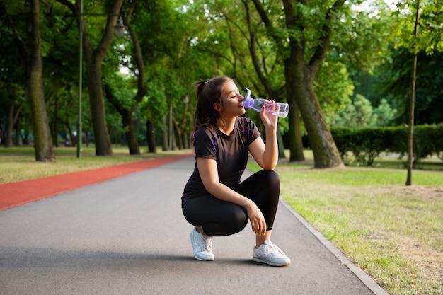 Młoda kobieta z nadwagą uprawia sport na świeżym powietrzu.
