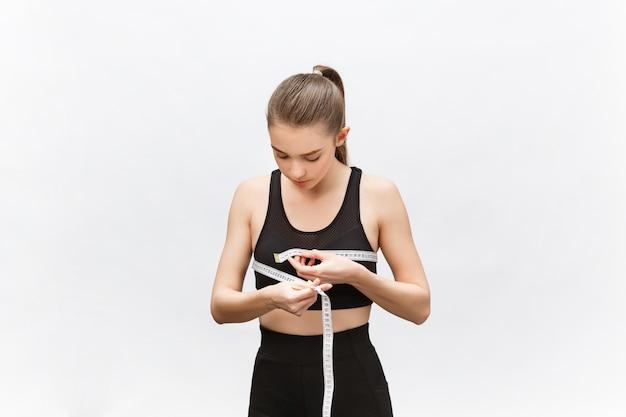 Młoda kobieta z nadwagą w sportowej bluzce ze smutkiem patrzy na wynik pomiaru talii