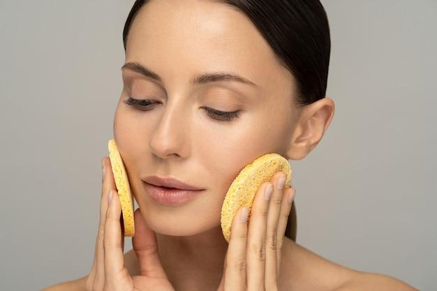 Młoda kobieta z nagim makijażem i nagimi ramionami myje twarz gąbką złuszczającą na białym tle