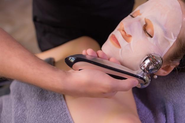 Młoda kobieta z nagimi ramionami za pomocą masażu twarzy, stojąc na białym tle na brązowym tle i odwracając wzrok.
