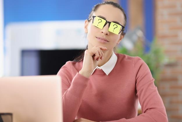 Młoda kobieta z naklejkami ze znakiem zapytania na okularach siedzi w biurze, szukając odpowiedzi na pytania