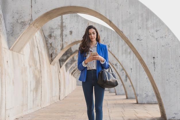 Młoda kobieta z niebieską kurtkę sprawdzenia jej telefonu komórkowego