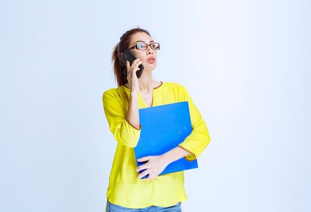 Młoda kobieta z niebieską teczką rozmawia przez telefon i wygląda na niezadowoloną