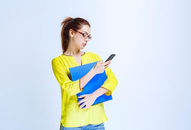 Młoda kobieta z niebieską teczką sprawdza jej wiadomości