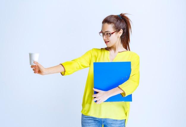 Młoda kobieta z niebieską teczką trzymająca białą, jednorazową filiżankę