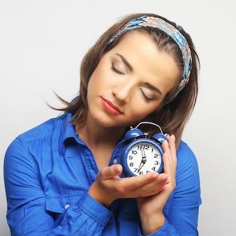 Młoda kobieta z niebieskim budzikiem