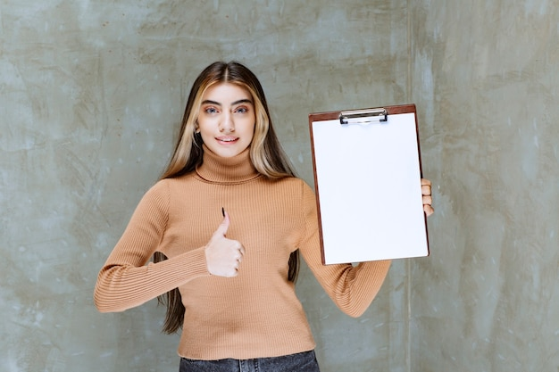 Młoda kobieta z notatnikiem pokazuje kciuk do góry na kamieniu