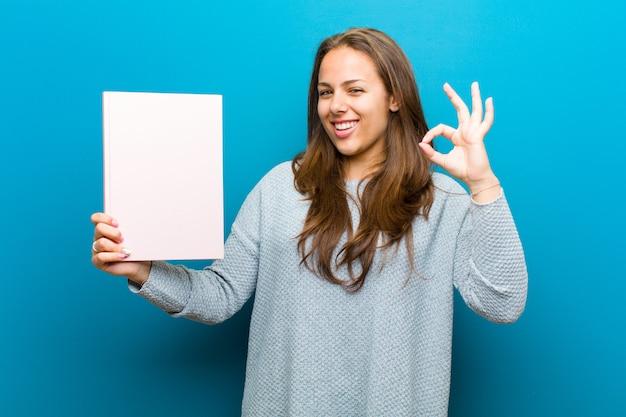 Młoda kobieta z notatnikiem przeciw błękitnemu tłu
