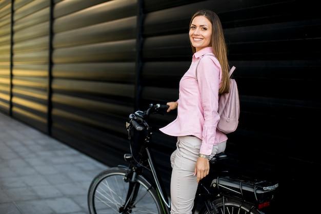 Młoda kobieta z nowoczesnym elektrycznym rowerem miejskim jako czysty zrównoważony transport miejski