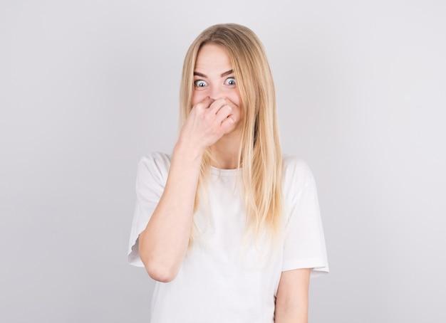 Młoda kobieta z obrzydzeniem na twarzy szczypie nos na białym tle. wyraz twarzy negatywnych emocji.