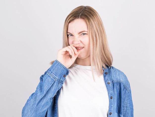 Młoda kobieta z obrzydzeniem na twarzy szczypie nos. wyraz twarzy negatywnych emocji.