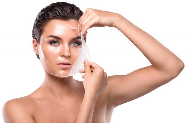 Młoda kobieta z oczyszczającą maską na jej twarzy