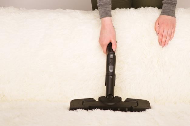 Młoda kobieta z odkurzaczem parowym czyści dywan na kanapie