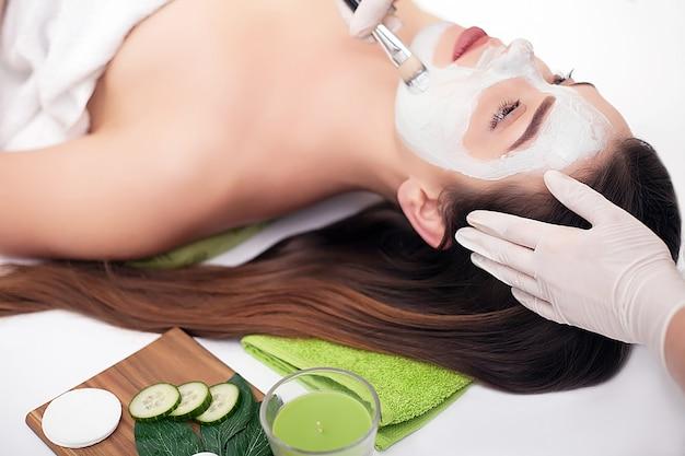 Młoda kobieta z odżywczą maską na twarz w salonie kosmetycznym