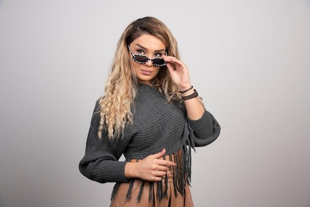 Młoda kobieta z okularami, patrząc na jej stronie.