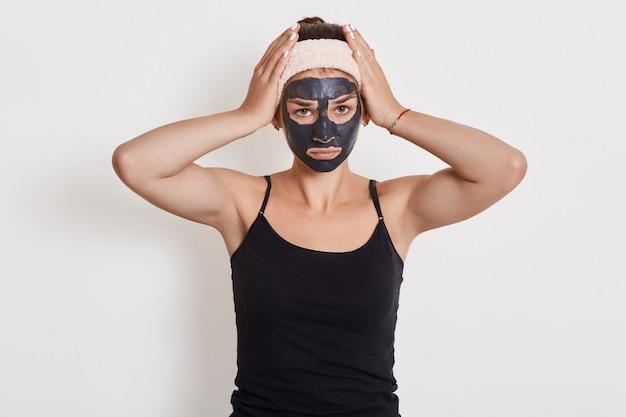 Młoda kobieta z opaską na sobie nosi maseczkę kosmetyczną i pozowanie na białej ścianie cierpi na ból głowy lub migrenę, trzymając ręce na głowie.