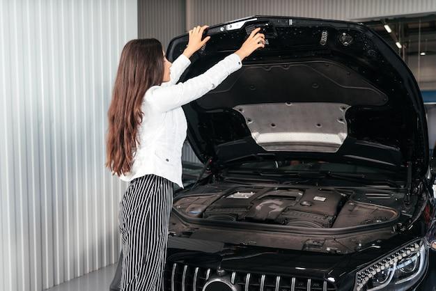 Młoda kobieta z otwartą maską w garażu zaglądająca pod maskę samochodu