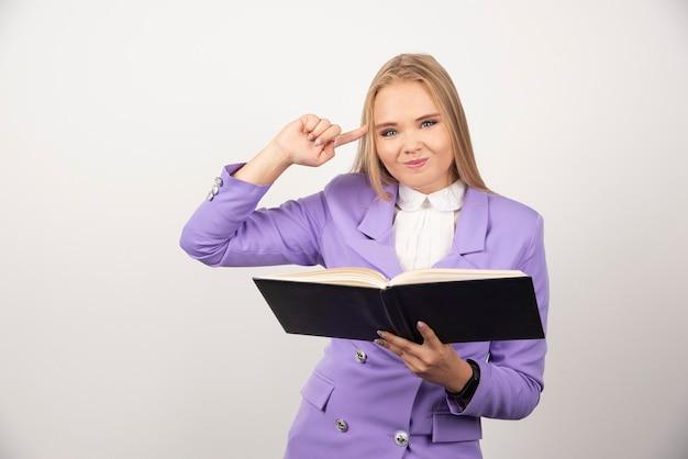 Młoda kobieta z otwartą tabletką na białym tle.