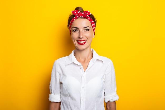 Młoda kobieta z pałąkiem na głowę, uśmiechając się na żółtej ścianie. transparent.