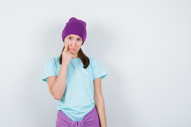 Młoda kobieta z palcem wskazującym na policzku, wygięte usta w niebieskiej koszulce, fioletowa czapka i posępnie wyglądająca. przedni widok.