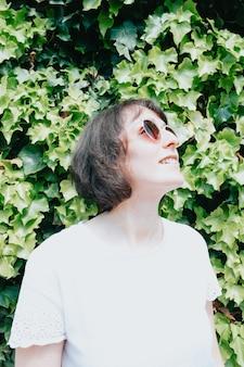 Młoda kobieta z parą okularów przeciwsłonecznych do aparatu, uśmiechając się, koncepcja lato