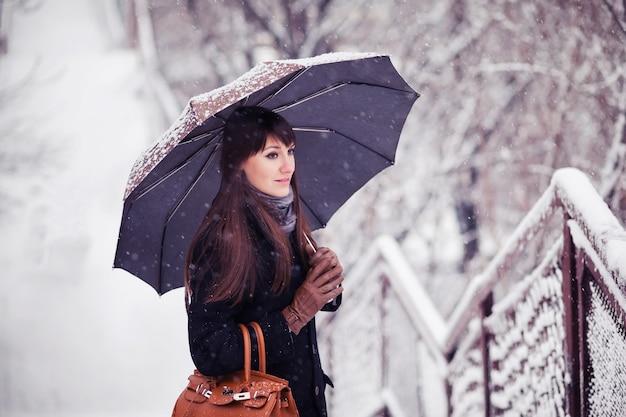 Młoda kobieta z parasolem w śniegu, retro stonowany obraz