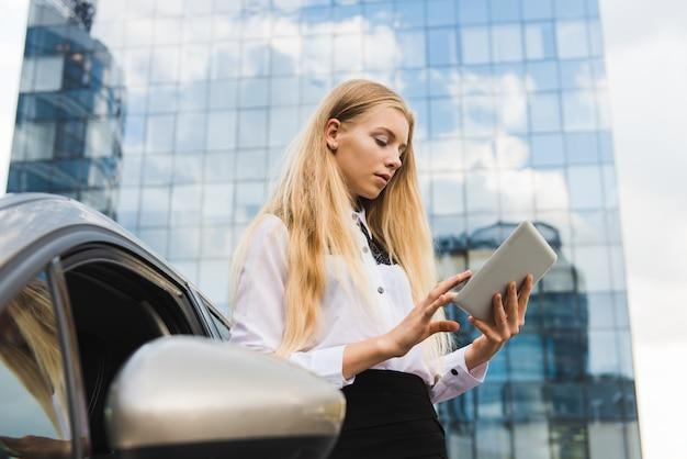 Młoda kobieta z pastylką blisko samochodu outdoors