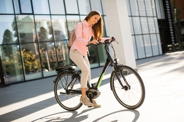 Młoda kobieta z pastylką i rowerem plenerowymi