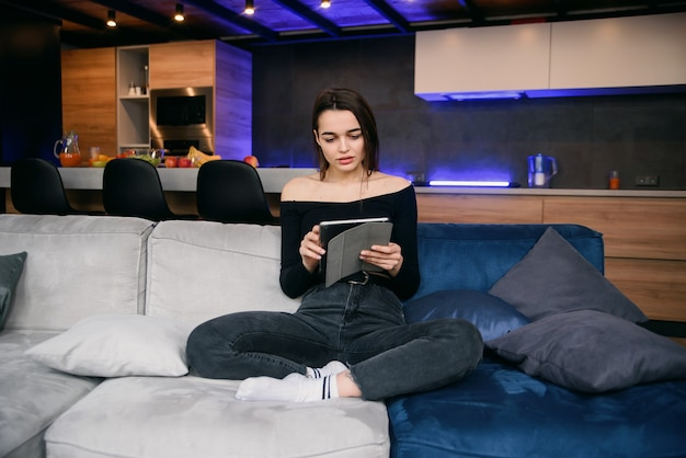 Młoda kobieta z pastylka komputerem osobistym na kanapie