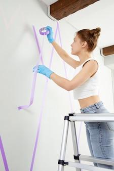 Młoda kobieta z pędzlem malującym ścianę w nowej koncepcji dekoracji domu home