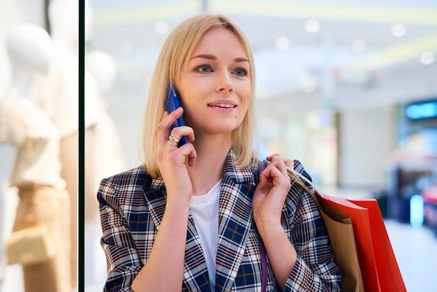 Młoda kobieta z pełnymi torbami na zakupy rozmawia przez telefon komórkowy