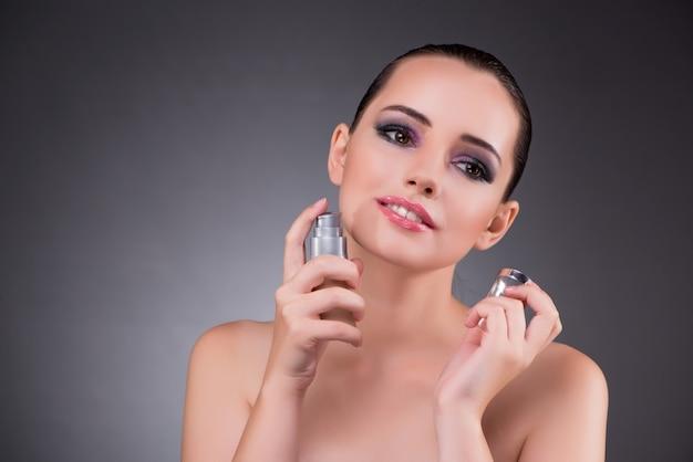 Młoda kobieta z perfumami w pięknie