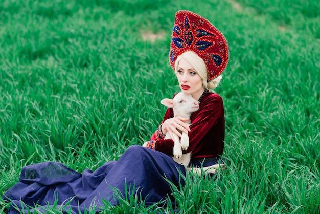 Młoda kobieta z piękną twarzą i blond kręconymi włosami w stroju ludowym, trzymając ładny biały mały baranek