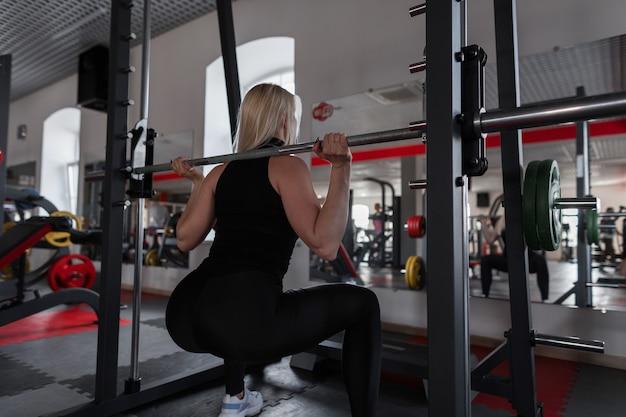 Młoda kobieta z pięknym ciałem robi ciężkie ćwiczenia na siłowni z metalową podstrunnicą