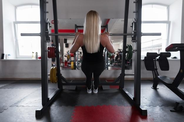 Młoda kobieta z pięknym ciałem robi ćwiczenia dłoni w nowoczesnej siłowni
